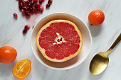 Close of view of grapefruit half with defocused fruit in background.