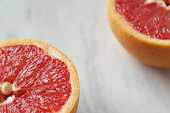Two portions of grapefruit halves frame white marble copy space.