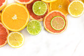 Vibrant juicy citrus fruits on a white marble texture with copy space. Grapefruit, lime, lemon, and orange slices