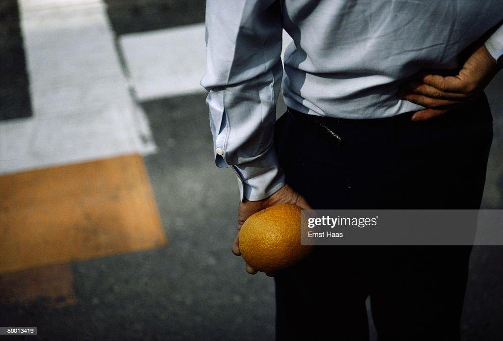 Premium Rates Apply. A man holding a grapefruit behind his back, Japan, May 1983.