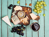 Grapes, red wine, cheeses, honey and nuts over shabby grunge wood. Top view.
