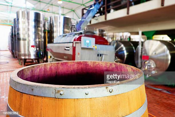 Grape-stained wine barrel with modern winery equipment in background