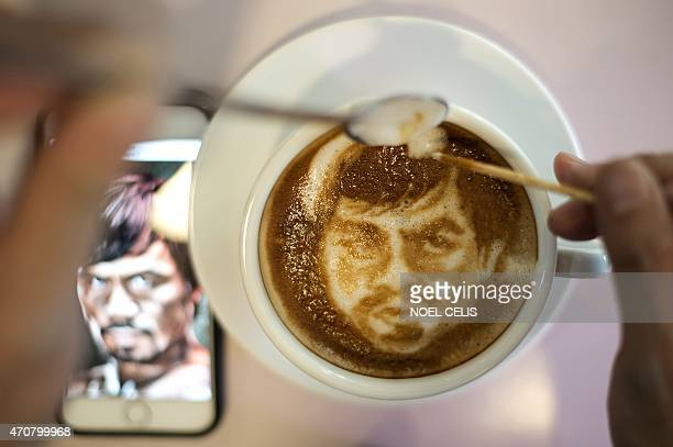 Graphic artist and barista Zach Yonzon uses coffee latte milk froth to illustrate a depiction of Philippine boxing icon Manny Pacquiao at his cafe in...