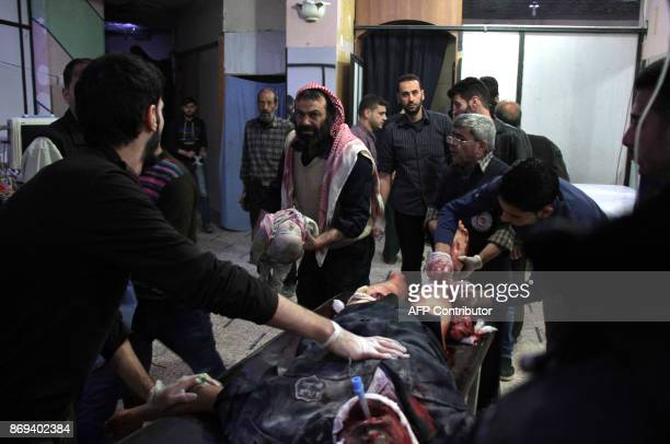 Graphic content / A badly wounded Syrian man is treated on a stretcher as a rescuer carries into the room a lifeless baby on November 2 2017 at a...