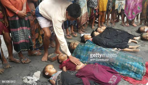 Graphic content / A Bangladeshi man touches the body of a child on August 31 one of a number of people who drowned after their boat capsized on the...