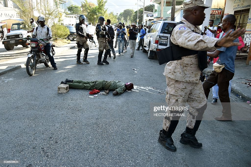 Graphic content / A body of a dead man lies on the ground after clashes between police and demonstrators during a protest agaist President Michel Martelly and for a transitional government in Port-au-Prince on February 5, 2016. President Michel Martelly's term ends February 7, and with no successor in place, Haiti is facing constitutional crisis. Haiti's electoral authority postponed the planned January 24 presidential run-off amid mounting opposition street protests and voting fraud allegations. / AFP / HECTOR