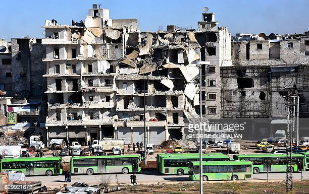 Graphic content / A general view shows buses waiting in front of destroyed buildings during an evacuation operation of rebel fighters and their...