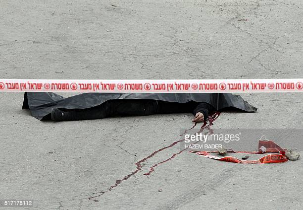 Graphic content / A general view shows the body of one of the two Palestinians who wounded an Israeli soldier in a knife attack before being shot...