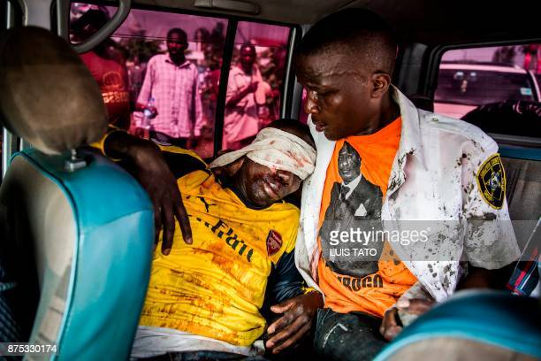 Graphic content / A Kenyan opposition party National Super Alliance supporter helps a man allegedly shot by Kenyan police during a demonstration on...