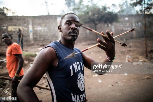 Graphic content / A man brandishes arrows during a street battle between Luo supporters of defeated opposition leader Raila Odinga and members of...