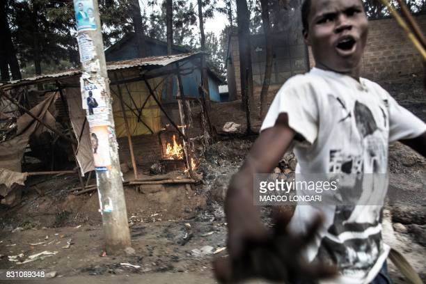 Graphic content / A man gestures to the camera as food stalls belonging to traders from the Kikuyu ethnic group are burning after they were set on...