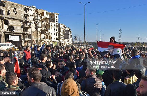 Graphic content / A man holds the Syrian flag bearing a portrait of the Syrian president as residents in a governmentheld area of Aleppo gather in...