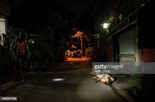 Graphic content / A man looks at a dead body of an alleged drug dealer on a street in Manila on July 12 2016 The Philippine government's top lawyer...