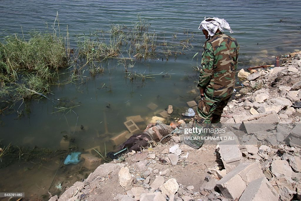 Graphic content / A member of Iraqi government special forces looks at a body floating along the shore of the Euphrates river as he patrols an area in the center of Fallujah, 50 kilometres (30 miles) from the Iraqi capital Baghdad, after Iraqi forces retook the embattled city from the Islamic State group on June 27, 2016. Iraqi forces took the Islamic State group's last positions in the city of Fallujah on June 26, 2016, establishing full control over one of the jihadists' most emblematic bastions after a month-long operation. ALI