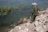 Graphic content / A member of Iraqi government forces looks at a body floating along the shore of the Euphrates river as he patrols an area in the...