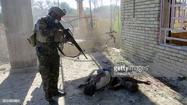 Graphic content / A member of Iraqi security forces look at bodies on the ground as they clear alSajarya district on the eastern outskirts of Ramadi...
