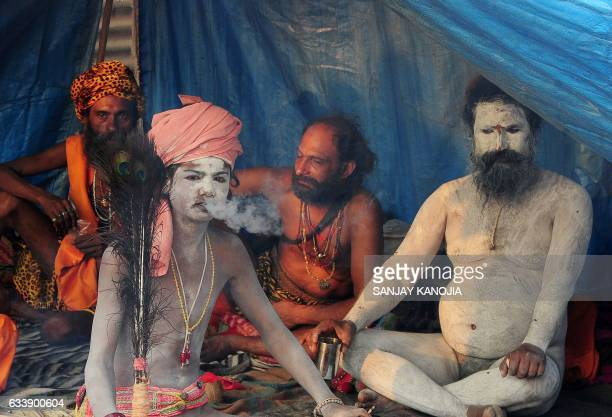 Graphic content / A novice Indian Sadhu smokes as he sits in a tent with other Sadhus during the Magh Mela festival in Allahabad on February 5 2017 /...
