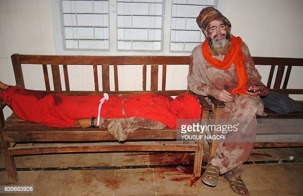 Graphic content / A Pakistani devotee covered with blood sits next to the body of a blast victim at a local hospital in the town of Sehwan in Sindh...