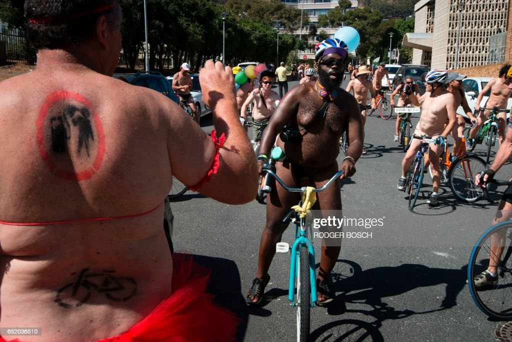 Graphic content / A participant, wearing a tutu, with body painting done, takes photos of other participants in the annual Naked Bike Ride(NBR), as they ride bicycle through the city, wearing underwear, body paint or nothing at all, on March 11, 2017, in Cape Town. This event was organised to raise awareness for safe cycling, create enthusiasm for using bycicles as a mode of transport, and protest the ongoing use of fossil-fuel to power transport. This event is similar to many NBR events organised in other cities in the world. /