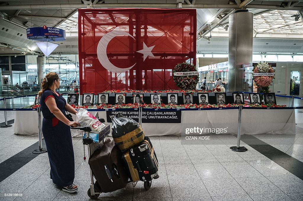 A passenger looks at the pictures of killed airport employees at Ataturk airport international terminal in Istanbul on June 30, 2016 two days after the triple suicide bombing and gun attack occurred at Istanbul's Ataturk airport. The death toll from the triple suicide bombing and gun attack that occurred on June 28, 2016 at Istanbul's Ataturk airport has risen to 43 including 19 foreigners. The government has pointed the finger of blame at the Islamic State group and Turkish police rounded up 13 suspected IS jihadists in raids at 16 different locations across Istanbul on June 30. / AFP / OZAN