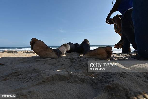 Graphic content / A photo taken on March 13 2016 shows the body of a man on the beach after heavily armed gunmen opened fire at a hotel in the Ivory...