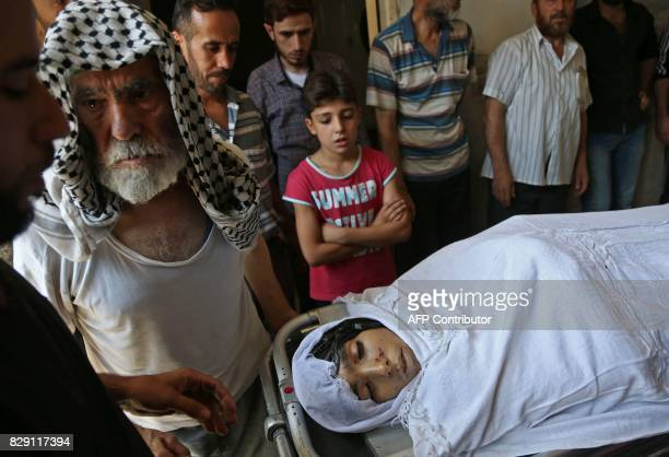 Graphic content / A picture taken on August 10 2017 shows the family of a Syrian child who was reportedly killed during regime shellings in the...