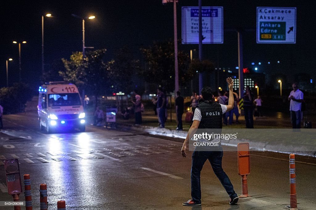 Graphic content / A policeman gestures at an ambulance after two explosions followed by gunfire hit the Turkey's biggest airport of Ataturk in Istanbul, on June 28, 2016. At least 10 people were killed on June 28, 2016 evening in a suicide attack at the international terminal of Istanbul's Ataturk airport, Turkish Justice Minister Bekir Bozdag said. Turkey has been hit by a string of deadly attacks in the past year, blamed on both Kurdish rebels and the Islamic State jihadist group. / AFP / OZAN