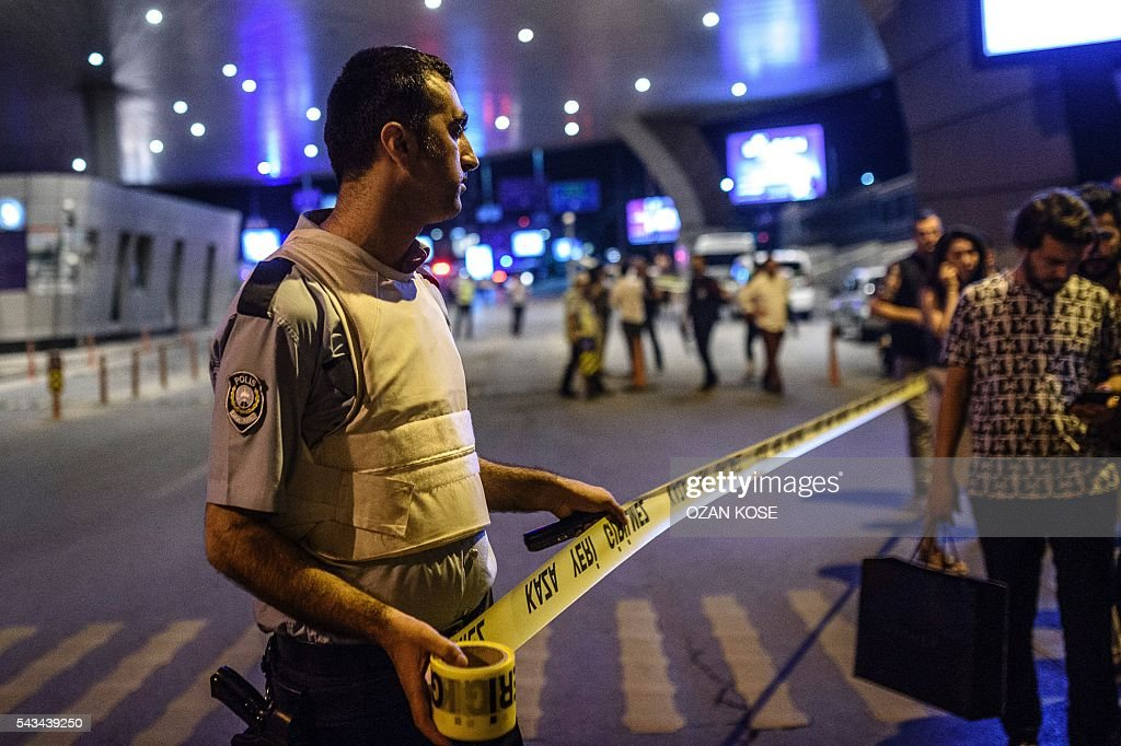 Graphic content / A policeman sets up a security perimeter as people leave the airport after two explosions followed by gunfire hit the Turkey's biggest airport of Ataturk in Istanbul, on June 28, 2016. At least 10 people were killed on June 28, 2016 evening in a suicide attack at the international terminal of Istanbul's Ataturk airport, Turkish Justice Minister Bekir Bozdag said. Turkey has been hit by a string of deadly attacks in the past year, blamed on both Kurdish rebels and the Islamic State jihadist group. / AFP / OZAN