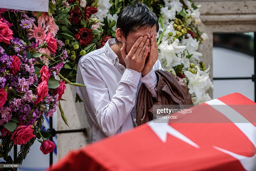 A relative of suicide attack victim Hamidullah Safar mourns next to his coffin covered with Turkish national flag on June 30, 2016 in Istanbul during his funeral two days after a suicide bombing and gun attack targeted Istanbul's airport, killing at least 36 people. The death toll from the triple suicide bombing and gun attack that occurred on June 28, 2016 at Istanbul's Ataturk airport has risen to 43 including 19 foreigners. The government has pointed the finger of blame at the Islamic State group and Turkish police rounded up 13 suspected IS jihadists in raids at 16 different locations across Istanbul on June 30. KOSE