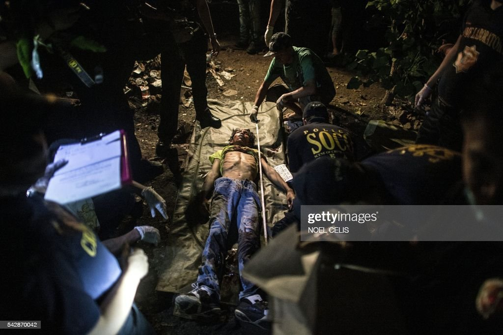 Graphic content / A suspected drug pusher lies dead as police crime scene operatives gather forensic evidence after three suspected drug pushers were killed when a drug bust operation ended in a shootout with authorities in Manila early on June 25, 2016. Catholic Church leaders in the Philippines expressed alarm June 20 at a sharp rise in police killings of suspected criminals since the election of a firebrand president who has vowed a bloody war on crime. Their condemnation flies in the face of Philippine president-elect Rodrigo Duterte's call to police and even civilians to kill drug criminals. / AFP / NOEL