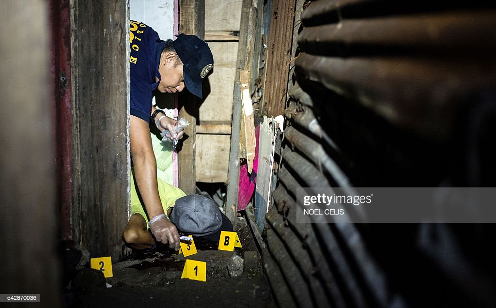 Graphic content / A suspected drug pusher lies dead on the ground as a police crime scene operative gathers forensic evidence after three suspected drug pushers were killed when a drug bust operation ended in a shootout with authorities in Manila early on June 25, 2016. Catholic Church leaders in the Philippines expressed alarm June 20 at a sharp rise in police killings of suspected criminals since the election of a firebrand president who has vowed a bloody war on crime. Their condemnation flies in the face of Philippine president-elect Rodrigo Duterte's call to police and even civilians to kill drug criminals. / AFP / NOEL