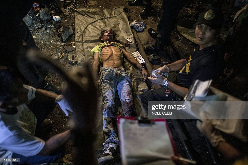 Graphic content / A suspected drug pusher lies dead on the ground as police crime scene operatives gather forensic evidence after three suspected drug pushers were killed when a drug bust operation ended in a shootout with authorities in Manila early on June 25, 2016. Catholic Church leaders in the Philippines expressed alarm June 20 at a sharp rise in police killings of suspected criminals since the election of a firebrand president who has vowed a bloody war on crime. Their condemnation flies in the face of Philippine president-elect Rodrigo Duterte's call to police and even civilians to kill drug criminals. / AFP / NOEL