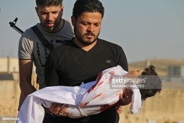 Graphic content / A Syrian father carries the body of his fouryearold son who was reportedly killed during shelling by Syrian government forces on a...