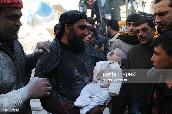 Graphic content / A Syrian man carries the body of a baby found in the rubble of a destroyed building following reported air strikes in...