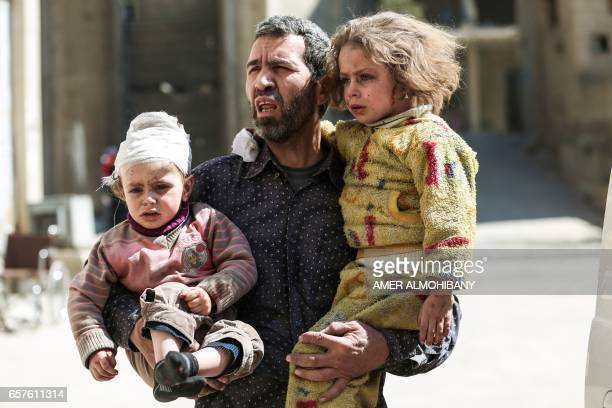 Graphic content / A Syrian man carries two injured children after a reported air strike in the rebelcontrolled town of Hamouria in the eastern Ghouta...