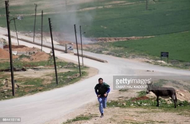 Graphic content / A Syrian medic runs for cover during the air strikes which hit a hospital in Khan Sheikhun a rebelheld town in the northwestern...