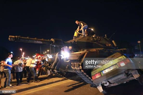 Graphic content / A tank crashes a car as people take streets in Ankara Turkey during a protest against military coup on July 16 2016 42 dead in...
