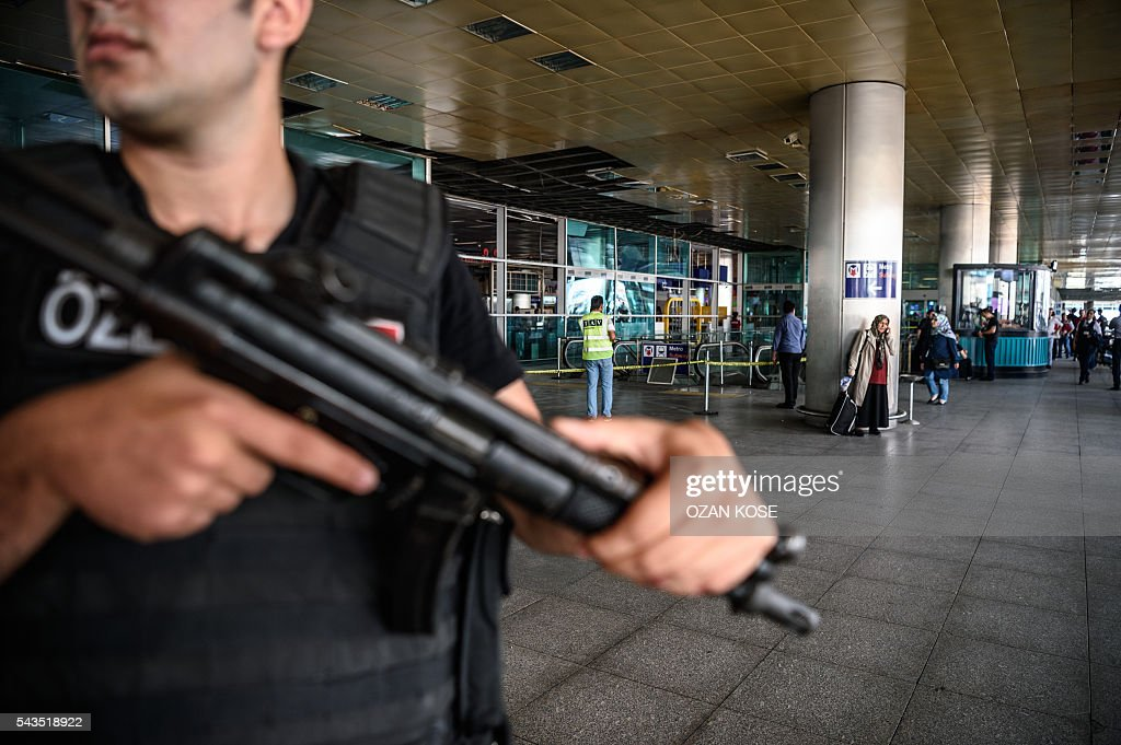A Turkish anti-riot police officer (L) stands guard as people walk past near the explosion site on June 29, 2016 at Ataturk airport International arrival terminal in Istanbul, a day after a suicide bombing and gun attack targeted Istanbul's airport, killing at least 36 people. A triple suicide bombing and gun attack that occurred on June 28, 2016 at Istanbul's Ataturk airport has killed at least 36 people, including foreigners, with Turkey's prime minister saying early signs pointed to an assault by the Islamic State group. / AFP / OZAN