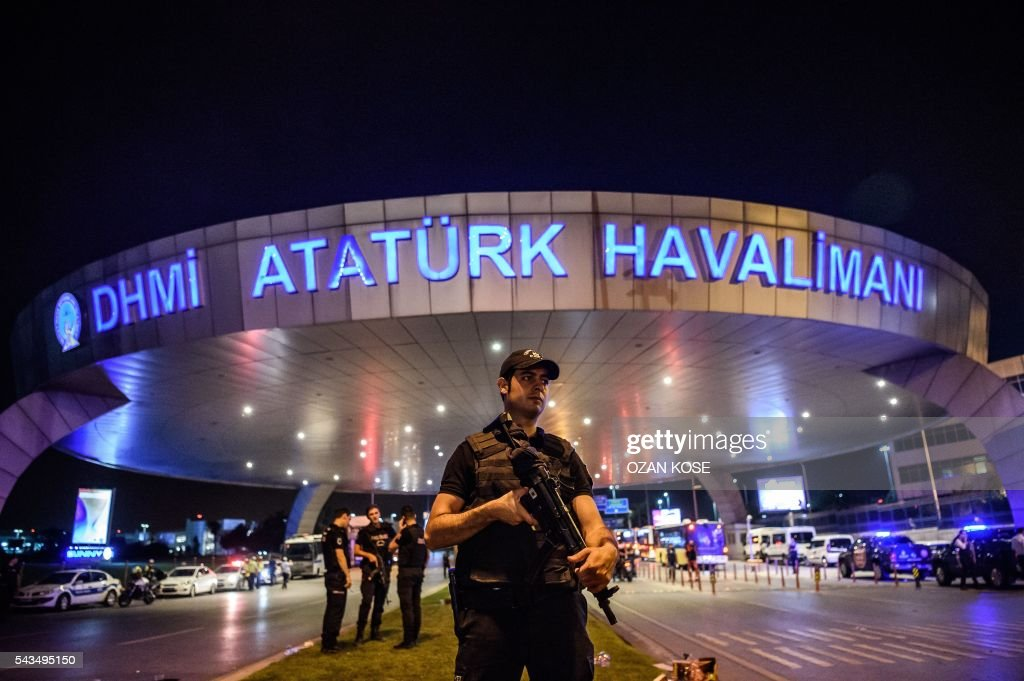 A Turkish riot police officer patrols Ataturk airport`s main enterance in Istanbul, on June 28, 2016, after two explosions followed by gunfire hit Turkey's largest airport, killing at least 10 people and injuring 20. All flights at Istanbul's Ataturk international airport were suspended on June 28, 2016 after a suicide attack left at least 36 people dead. / AFP / OZAN