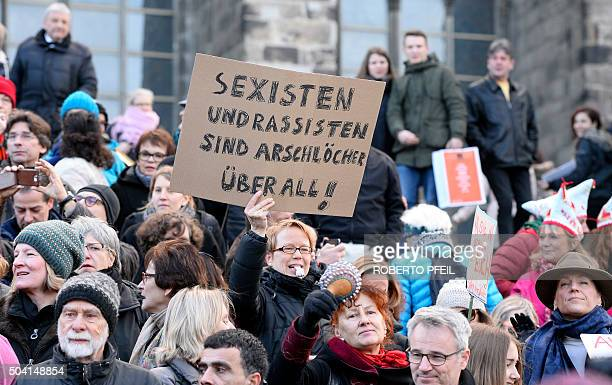 Graphic content / A woman holds up a sign reading 'Sexists and racists are assholeseverywhere' while taking part in a demonstration against violence...
