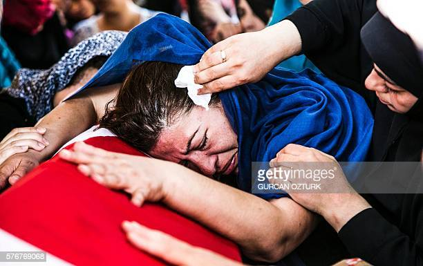 Graphic content / A woman lays her head on the coffin of a victim of the failed July 15 coup attempt during his funeral in Istanbul on July 17 2016...