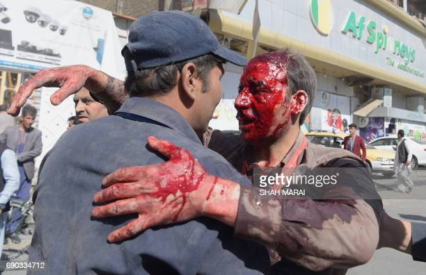 Graphic content / A wounded Afghan man receives assistance at the site of a car bomb attack in Kabul on May 31 2017 A massive blast rocked Kabul's...