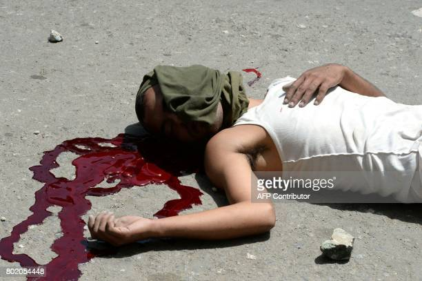 Graphic content / A young dead man lies in the street during lootings in Maracay Aragua state Venezuela on June 27 2017 / AFP PHOTO / Federico Parra