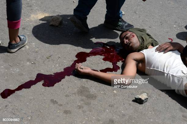 Graphic content / A young dead man lies in the street during lootings in Maracay Aragua state Venezuela on June 27 2017 / AFP PHOTO / Federico Parra...