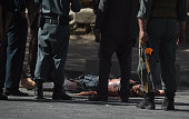 Graphic content / Afghan security personnel stands over the body of an attacker after a suicide bombing that targeted crowds of minority Shiite...