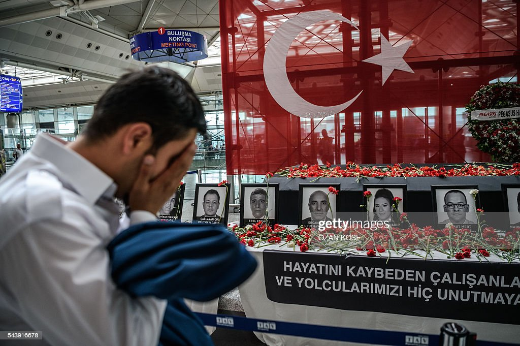 An airport employee mourns for his collegues as he looks at the pictures of killed airport employees at Ataturk airport international terminal in Istanbul on June 30, 2016 two days after the triple suicide bombing and gun attack occurred at Istanbul's Ataturk airport. The death toll from the triple suicide bombing and gun attack that occurred on June 28, 2016 at Istanbul's Ataturk airport has risen to 43 including 19 foreigners. The government has pointed the finger of blame at the Islamic State group and Turkish police rounded up 13 suspected IS jihadists in raids at 16 different locations across Istanbul on June 30. / AFP / OZAN