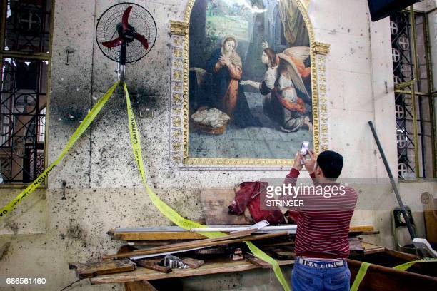 Graphic content / An Egyptian uses his cell phone to take pictures of the destruction debris and bloodstains on the walls and icon murals inside the...