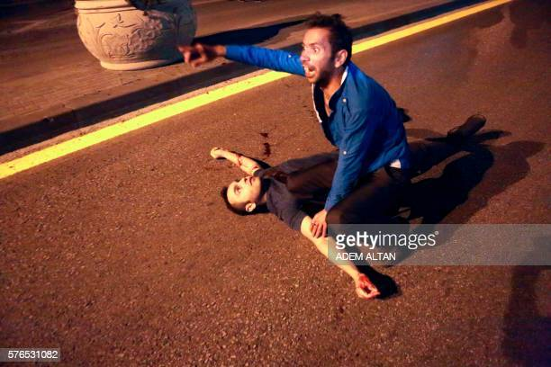 Graphic content / An injured man lies on a ground during a protest against military coup in Ankara Turkey on July 16 2016 42 dead in Ankara coup...
