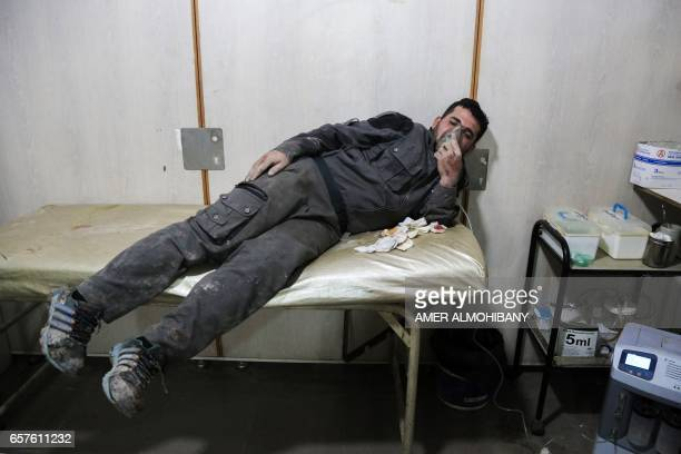 Graphic content / An injured Syrian breathes through an oxygen mask after a reported air strike in the rebelcontrolled town of Hamouria in the...