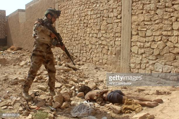 Graphic content / An Iraqi forces member holds a gun over a body during a military operation to push out Islamic State group jihadists from the...